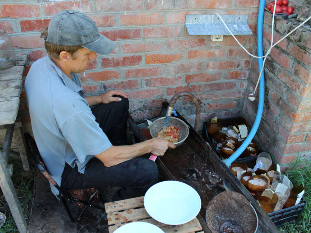 Ручная промывка сброженных семян с помощью сита.